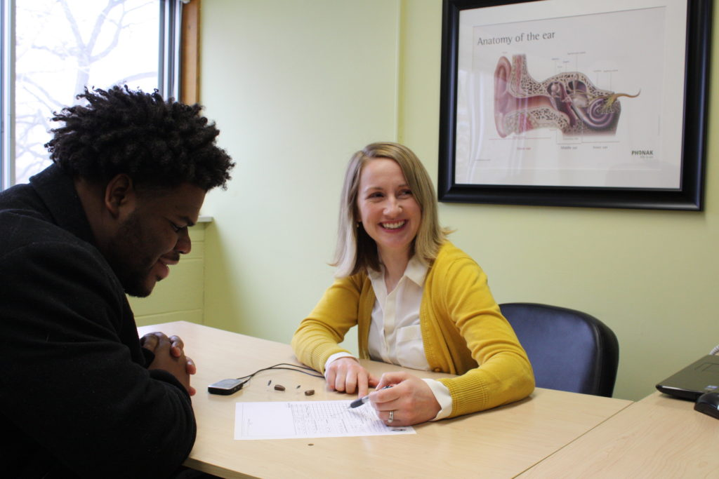 Dr. Rachel Lee, Audiologist at the UW Speech and Hearing Clinic, meets with a patient to discuss hearing aid options.