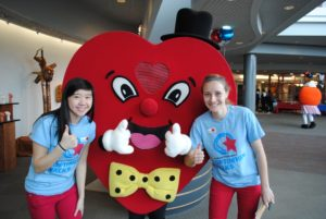 Two people with a heart mascot