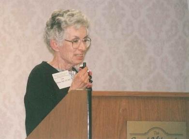 Lois Speaking at a Podium