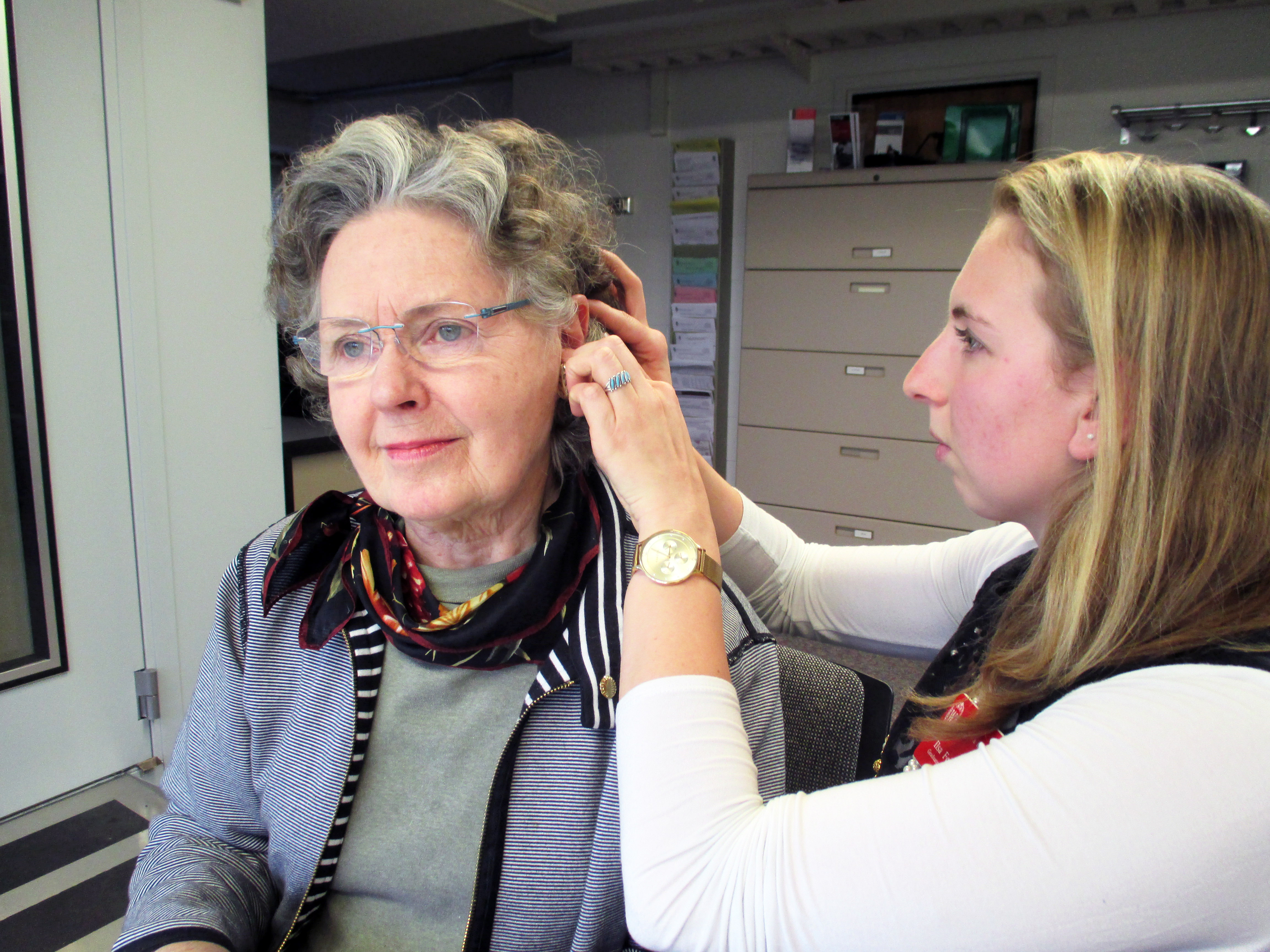 Audiology graduate student clinician fits an adult patient with a hearing aid.