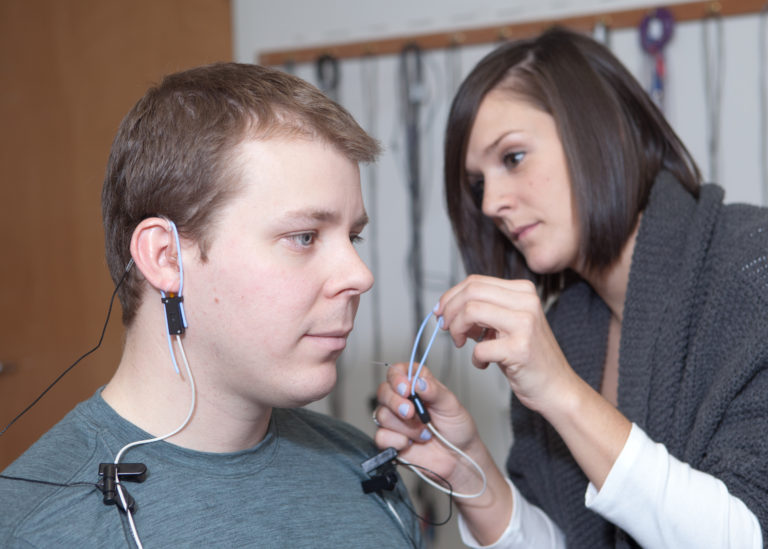 Audiology graduate student clinician performs real-ear verification measures on a hearing aid user.