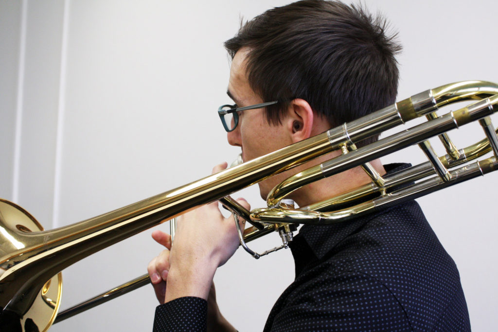 Music student wearing hearing protection while playing his trombone.