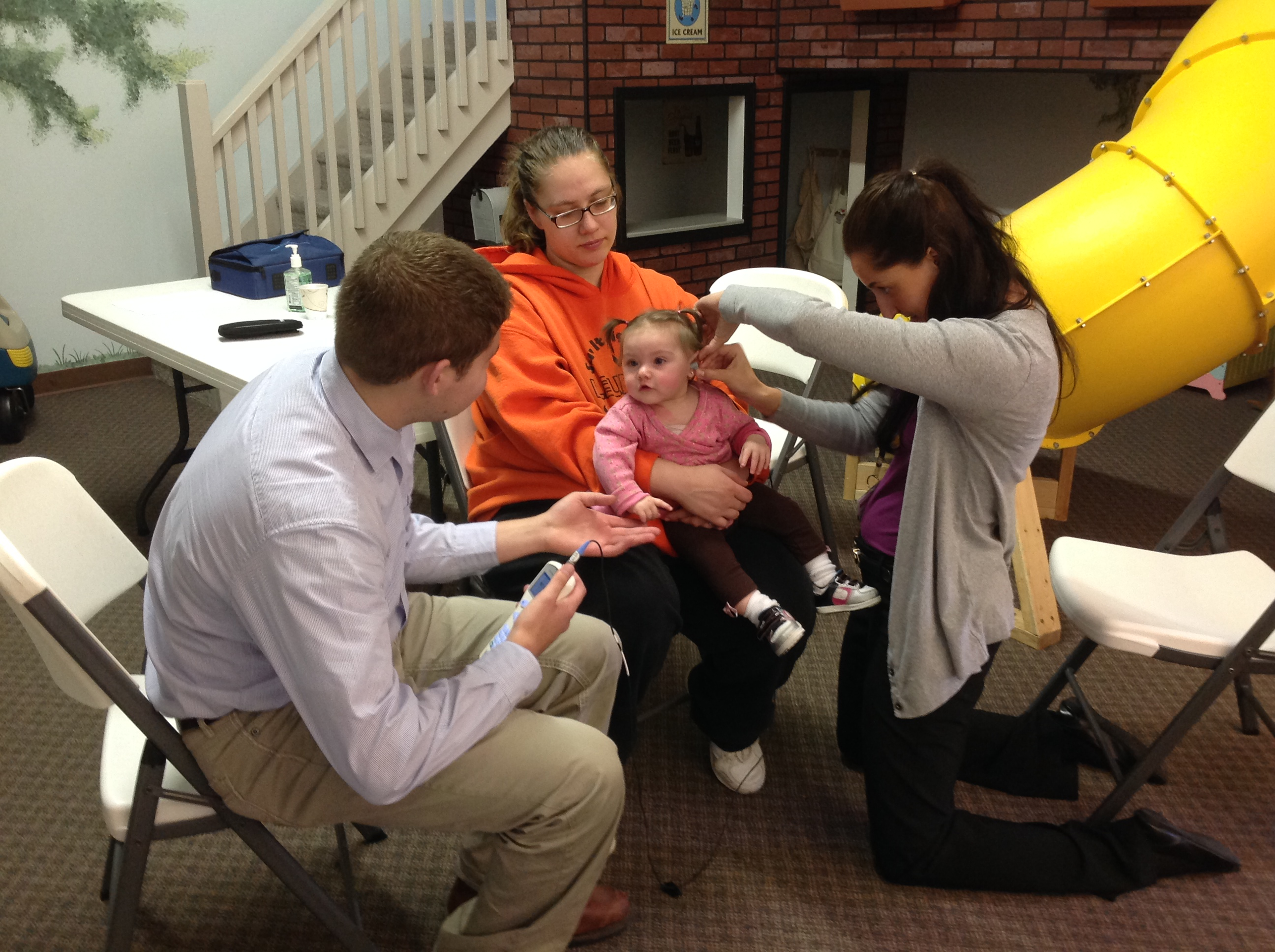 Au.D. students screening a child's hearing in the Early Head Start Program.