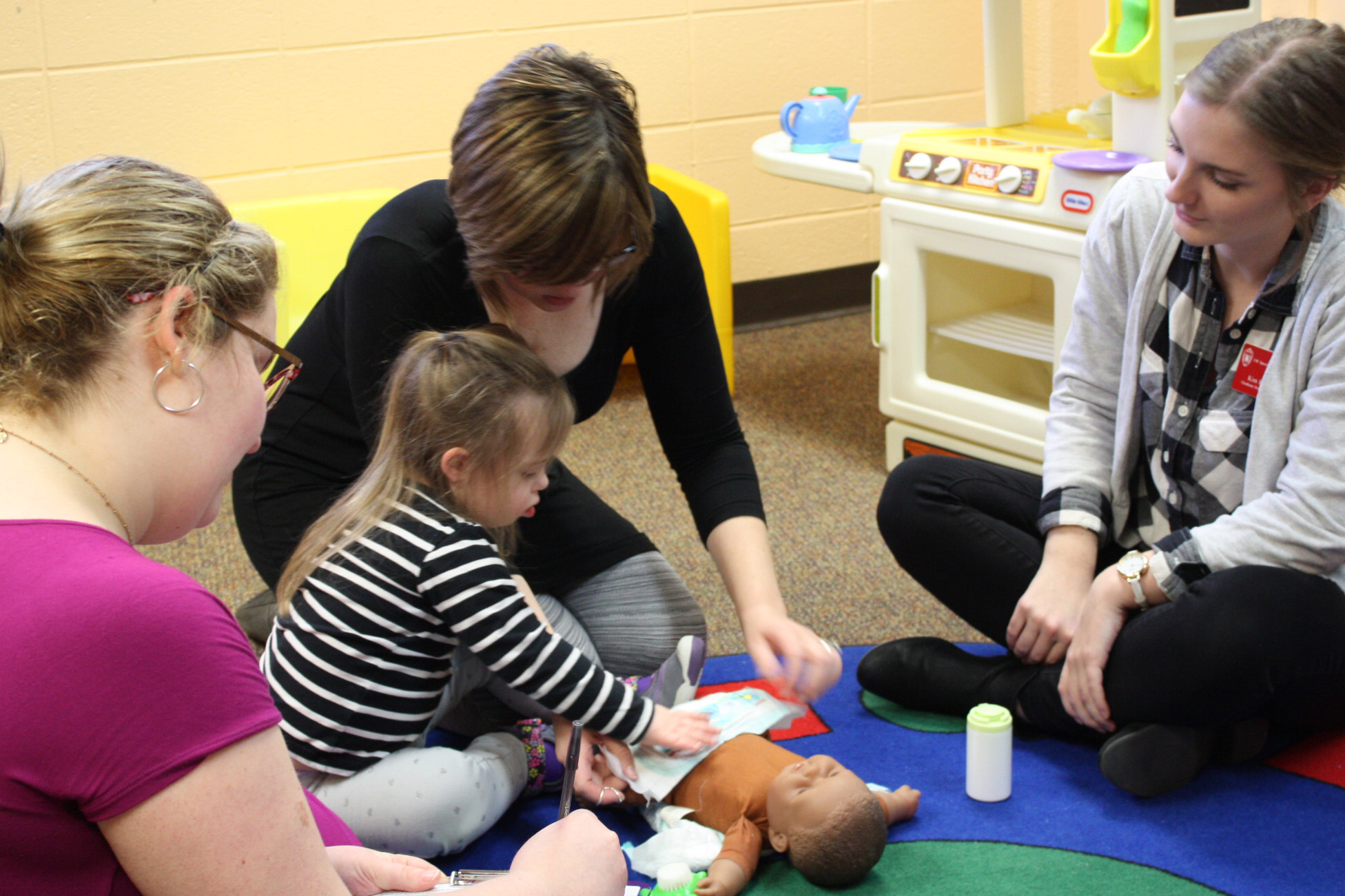 Student clinicians work with a family in a group session.