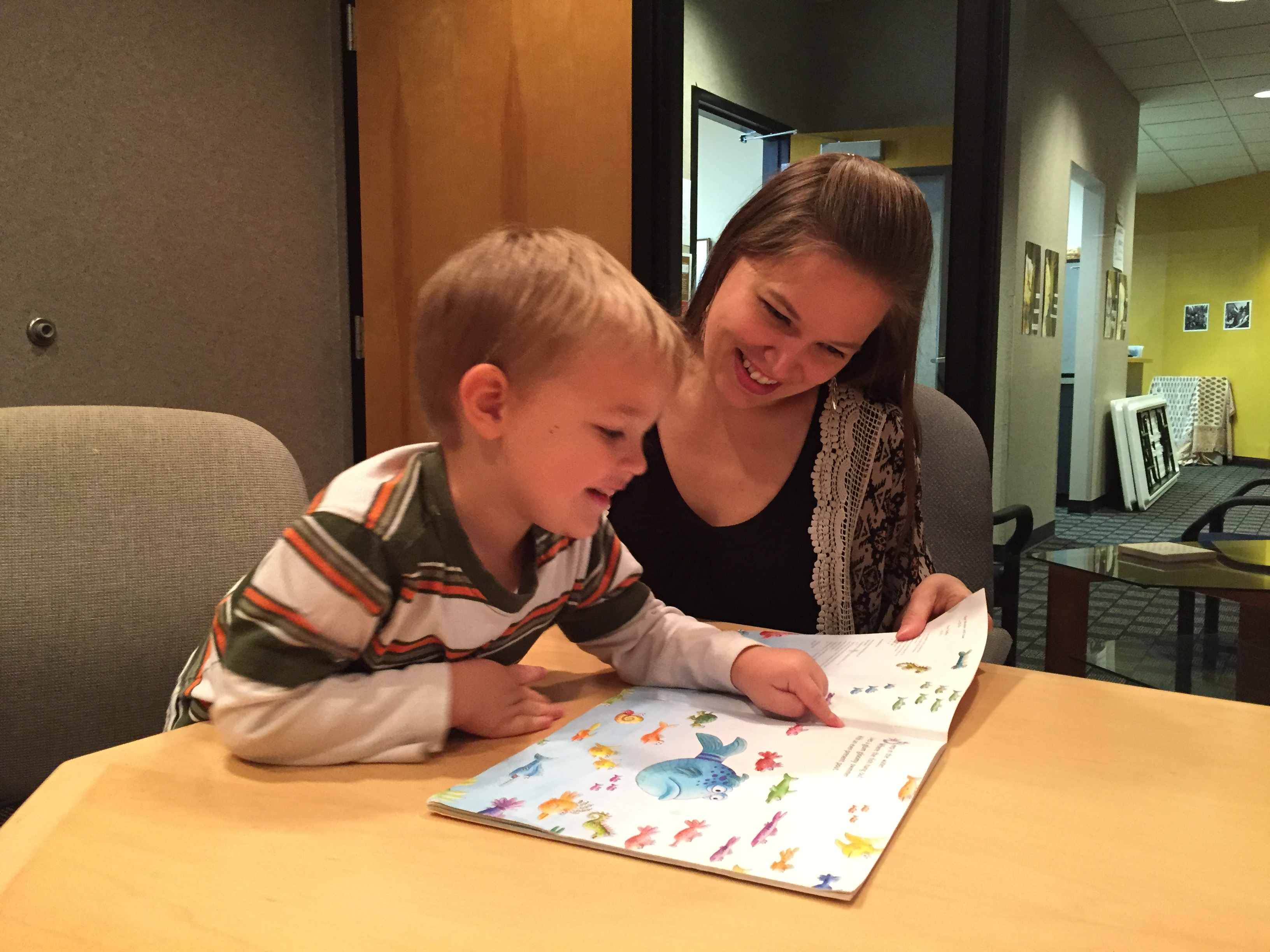 Dr. Courtney Seidel, Speech-Language Pathologist at the UW Speech and Hearing Clinic, reading with a child.