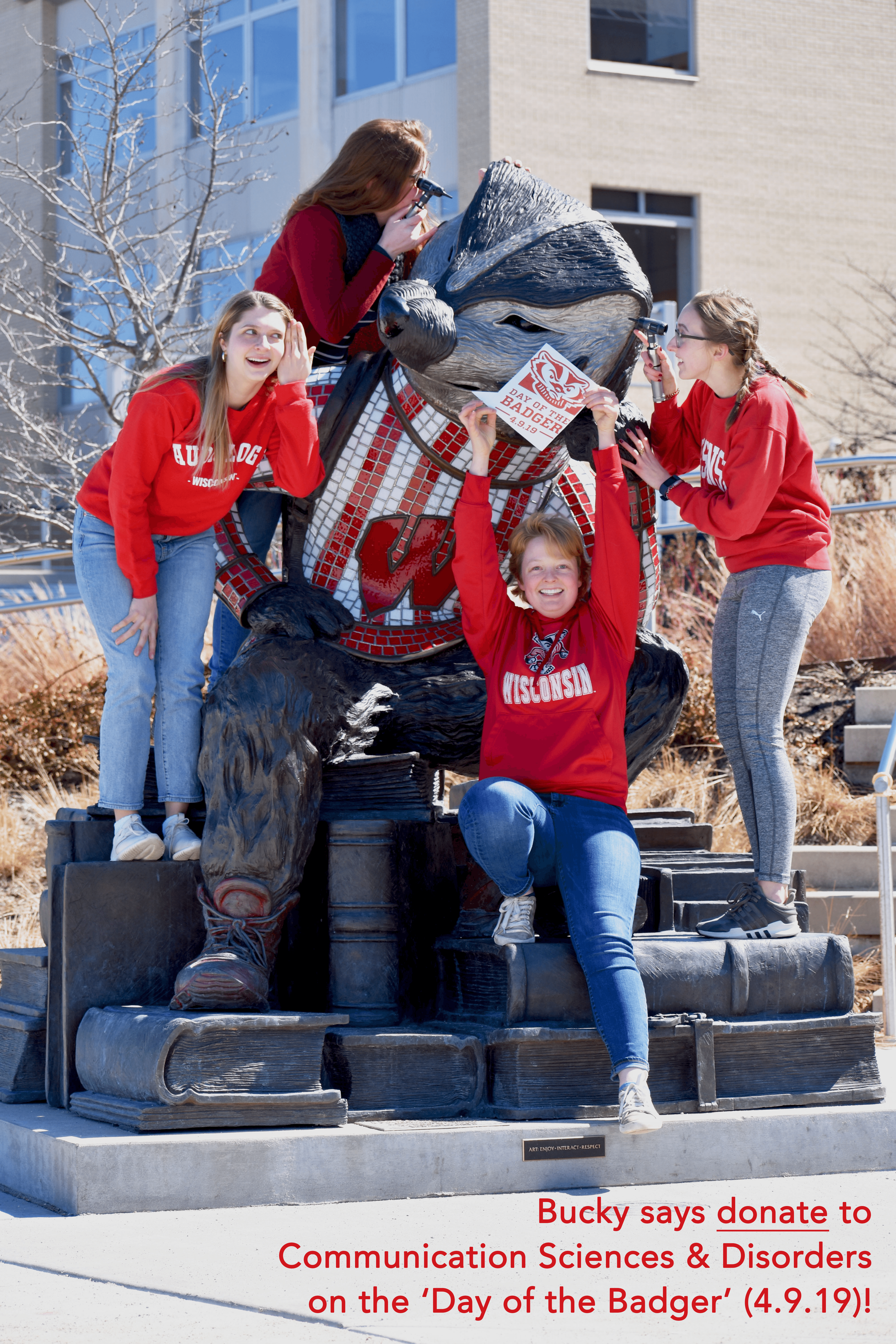 Audoliogy students posing with statue of Bucky Badger on the Memorial Union Terrace. Day of the Badger.