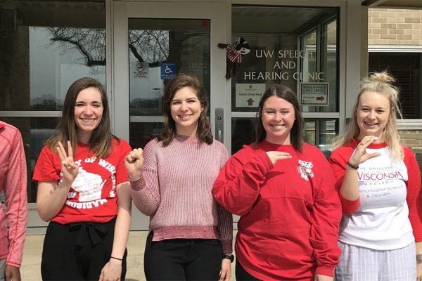 Graduate SLP students are all dressed in red, finger spelling UWSHC. Day of the badger.