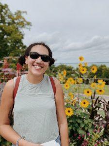 MS-SLP student Elizabeth Evans standing in front of sunflowers.