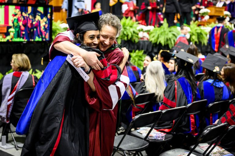 UW graduate Tanvi Thakkar (left), earning a PhD in communication sciences and disorders, receives a congratulatory hug from Ruth Litovsky, professor in communication sciences and disorders, during UW-Madison's spring commencement ceremony at the Kohl Center at the University of Wisconsin-Madison on May 10, 2019. The indoor graduation was attended by over 900 doctoral, MFA and medical student degree candidates, plus their guests. (Photo by Jeff Miller /UW-Madison)