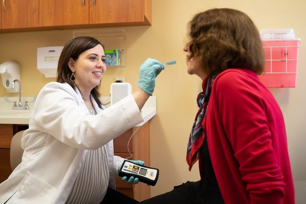 Dr. Rogus-Pulia performs a salivary test on a patient.