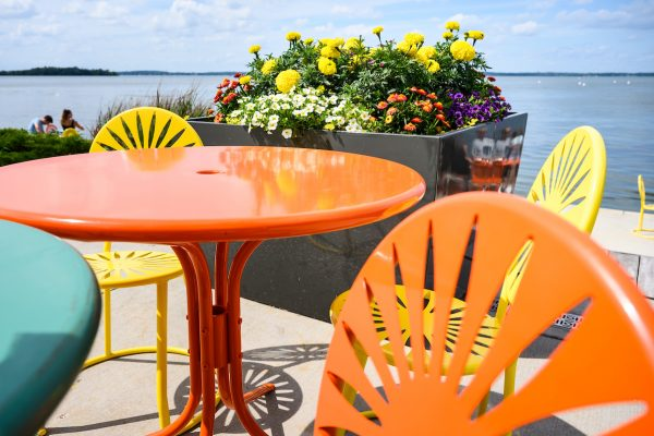 Recently cleaned and sanitized tables with sunburst-designed chairs are pictured with a planter of blooming flowers at the Memorial Union Terrace at the University of Wisconsin-Madison during summer on July 17, 2020. Patrons can enjoy physically distanced, reserved-table seating with food and drink service at the Terrace by making table reservations one to two days in advance via OpenTable. Masks and face coverings are required upon entry, while receiving service and while exiting. A majority of the campus, including the Memorial Union and Union South buildings, remain closed to the public due to the coronavirus (COVID-19) global pandemic. (Photo by Jeff Miller / UW-Madison)