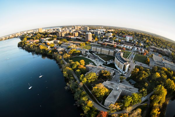 Taken with a fisheye lens, this photo depicts the northern shoreline of the University of Wisconsin-Madison campus along Lake Mendota and includes Dejope Residence Hall (bottom right) and the other lakeshore residence halls in an aerial view during autumn on Oct. 13, 2016. The photograph was made from a helicopter looking south. (Photo by Jeff Miller/UW-Madison)